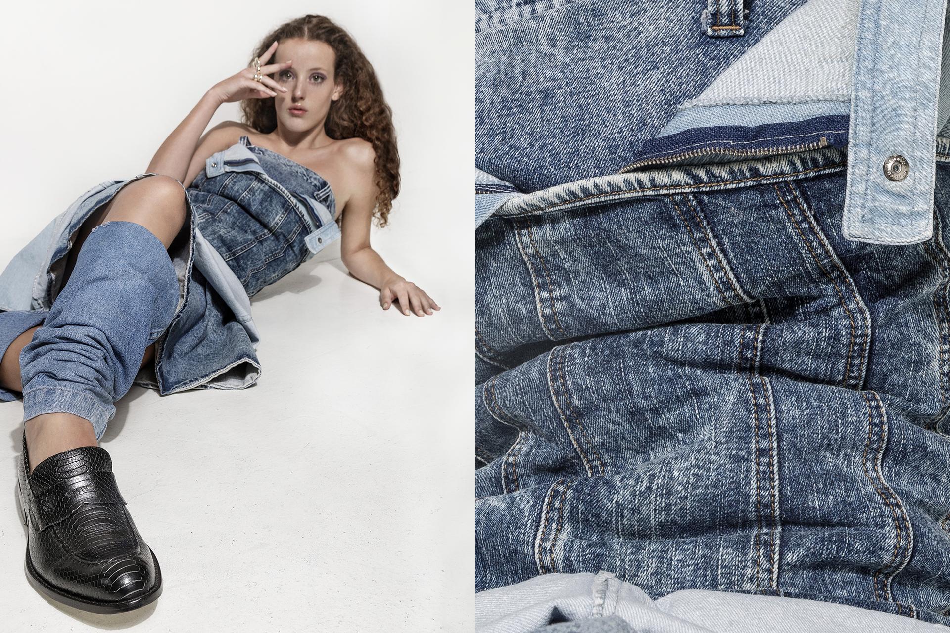 A modelo está deitada com as pernas em direção a camera. Ela veste jeans em diferentes tons de azul como vestido e também polaina. Usa sapatos pretos. A mão direita está no rosto, com a palma espalmada e a esquerda no chão.